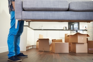 Man picking up couch with moving boxes in view - representing child custody and moving out of state